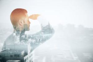 Young businessman looking into the distance on city background with copyspace. Research concept. Double exposure